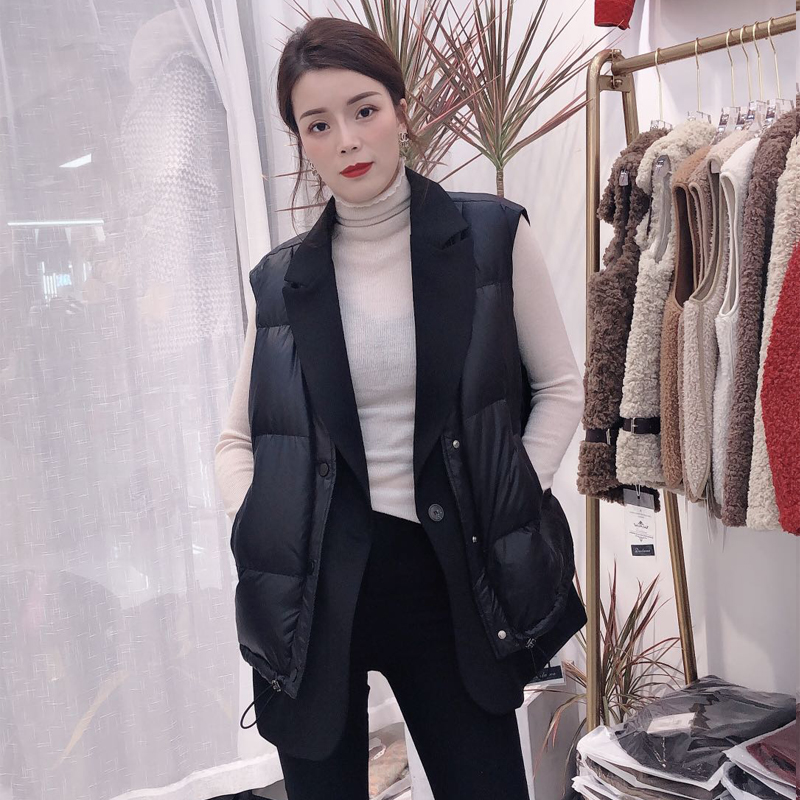 The woman in the down jacket is wearing a light white duck down 2020 autumn winter new fashion fake two-piece vest with a bumpy shoulder